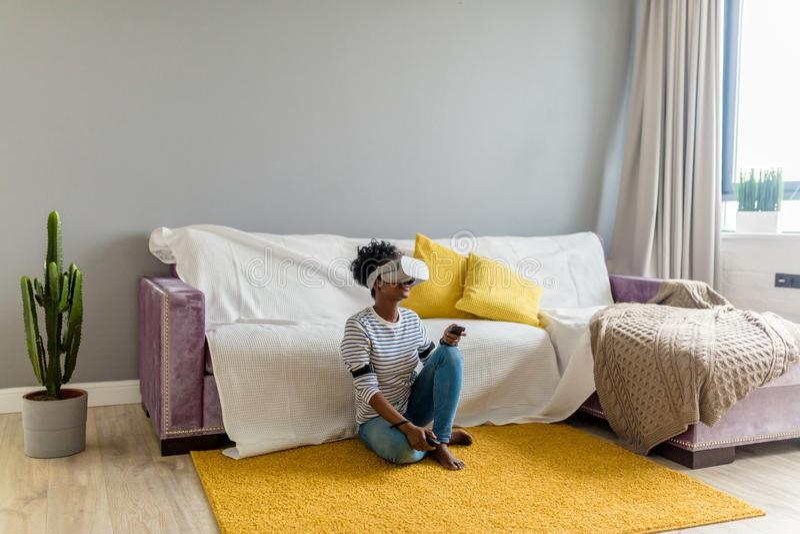Vidéo de observation de femme africaine utilisant des verres de VR avec à télécommande à la maison photographie stock