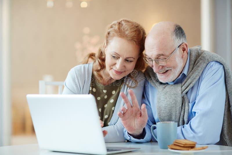 Vidéo de sourire de grands-parents causant par l'intermédiaire de l'ordinateur portable n images stock