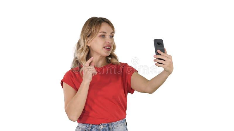 Vidéo femelle gaie d'enregistrement de blogger pour affronter la caméra du téléphone moderne tout en marchant sur le fond blanc images stock