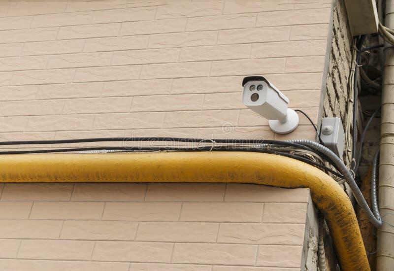Vidéo surveillance extérieure sur le coin de la brique pâle - wal rose photographie stock