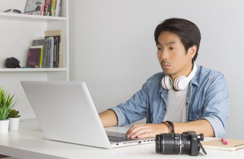 Vidéographe indépendant asiatique, édition d'un fichier multimédia par ordinateur portable dans son bureau images stock
