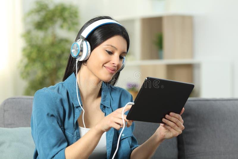 Vidéos de lecture rapide et de écoute de femme heureuse sur le comprimé photographie stock libre de droits