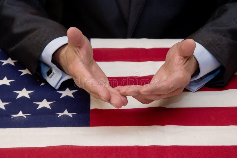Vid ett bord täckt med en amerikansk flagga håller en manlig affärsman och politiker ut sina händer för dialog arkivbilder