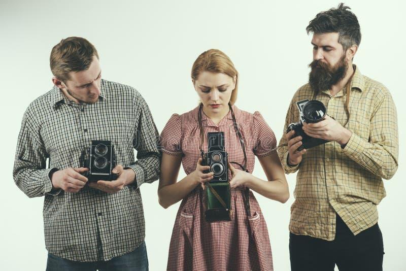 A vida é como uma câmera A mulher retro e os homens do estilo guardam câmeras análogas da foto Grupo de fotógrafo com câmeras ret foto de stock royalty free