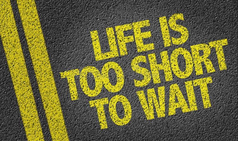 A vida é demasiado curto à espera escrita na estrada imagens de stock