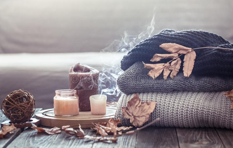 Vida acogedora de la calma del otoño con velas y un suéter imagenes de archivo