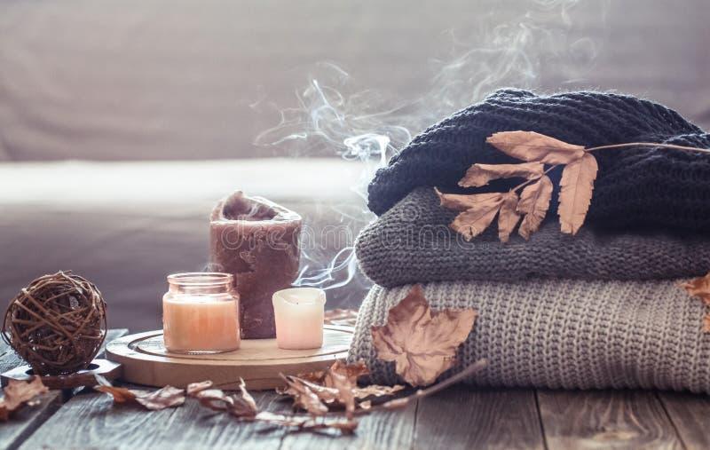 Vida acogedora de la calma del otoño con velas y un suéter fotografía de archivo libre de regalías