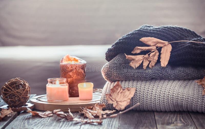 Vida acogedora de la calma del otoño con velas y un suéter foto de archivo