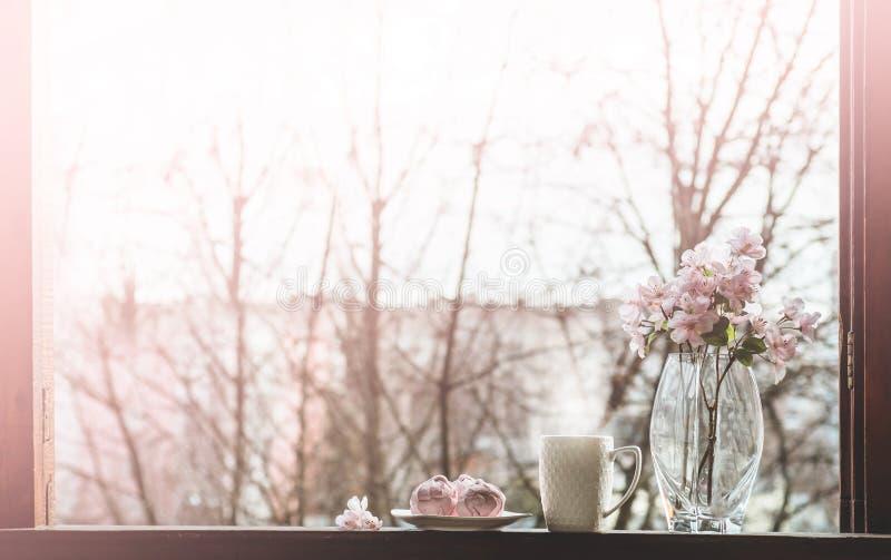 Vida acogedora de la calma de la primavera: taza de té caliente con el ramo de la primavera de flores en alféizar del vintage con imagenes de archivo