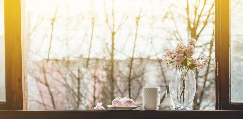Vida acogedora de la calma de la primavera: taza de té caliente con el ramo de la primavera de flores en alféizar del vintage con fotografía de archivo