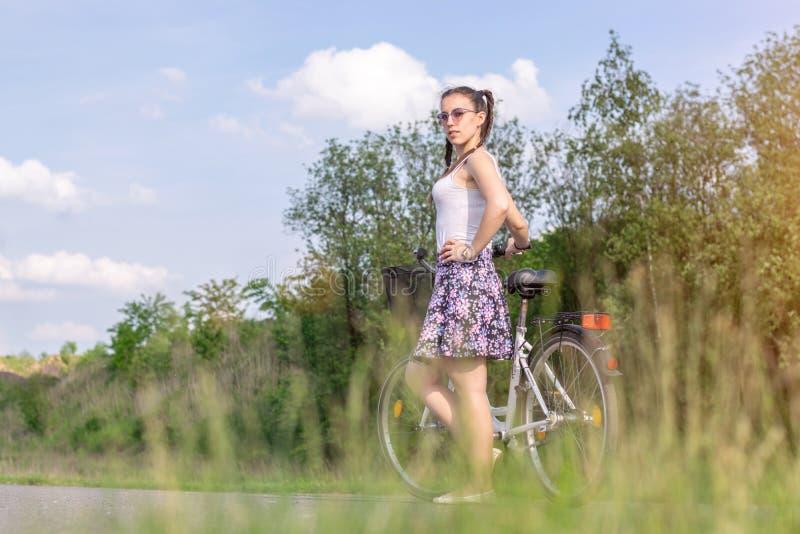 Vida activa Una mujer con una bici disfruta de la visi?n en la bicicleta del bosque del verano y el concepto de la ecolog?a foto de archivo
