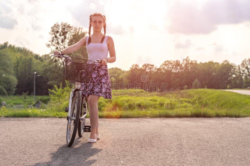 Vida activa Una mujer joven con el ciclo en la puesta del sol en el parque Bicicleta y concepto de la ecolog?a foto de archivo