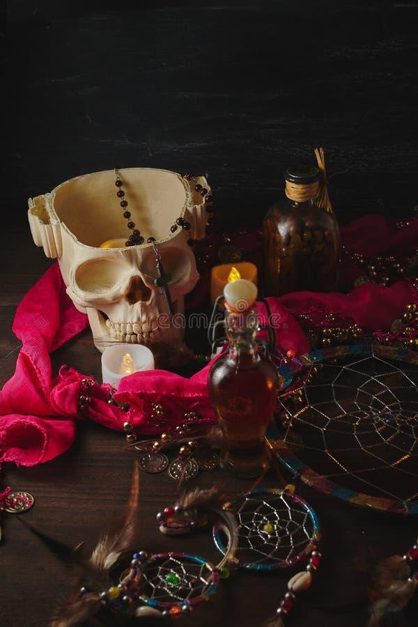 Vida aterradora con pociones, cráneo, mortero, botellas antiguas y velas en una mesa de brujas. Halloween o concepto esotérico imagen de archivo libre de regalías