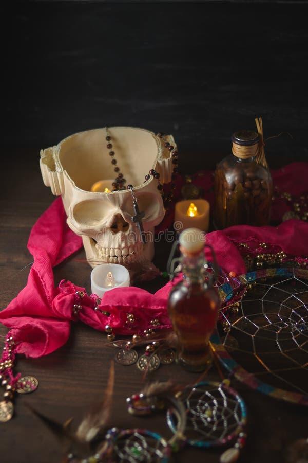 Vida aterradora con pociones, cráneo, mortero, botellas antiguas y velas en una mesa de brujas. Halloween o concepto esotérico foto de archivo