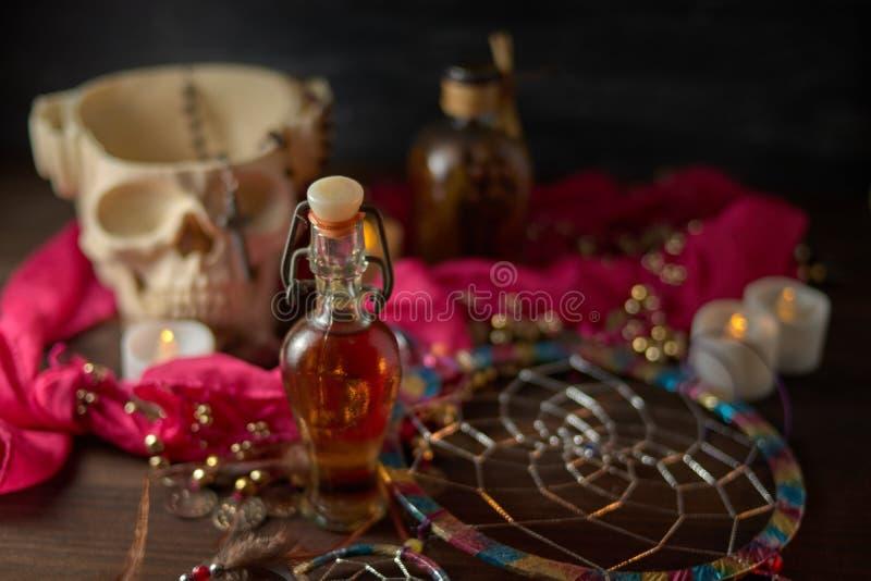Vida aterradora con pociones, cráneo, mortero, botellas antiguas y velas en una mesa de brujas. Halloween o concepto esotérico imagen de archivo