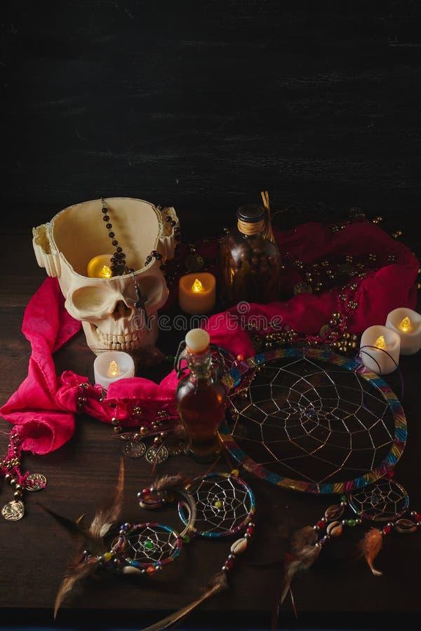 Vida aterradora con pociones, cráneo, mortero, botellas antiguas y velas en una mesa de brujas. Halloween o concepto esotérico imagenes de archivo