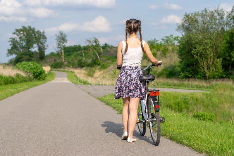 Vida ativa Uma jovem mulher com ciclagem no por do sol no parque Bicicleta e conceito da ecologia foto de stock royalty free
