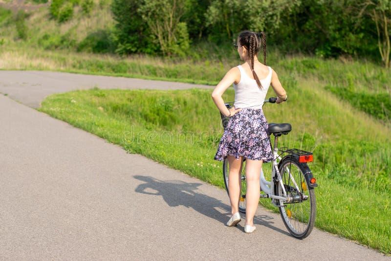 Vida ativa Uma mulher com uma bicicleta aprecia a vista na bicicleta da floresta do ver?o e no conceito da ecologia fotografia de stock