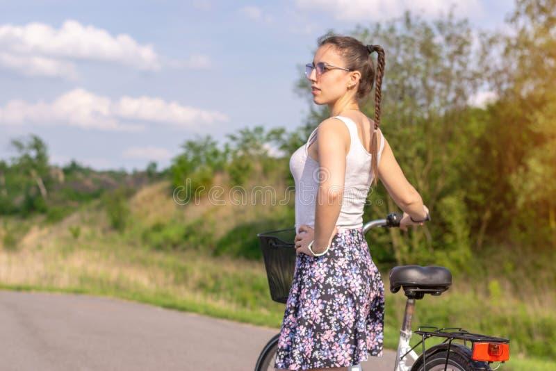Vida ativa Uma mulher com uma bicicleta aprecia a vista na floresta do ver?o fotografia de stock royalty free