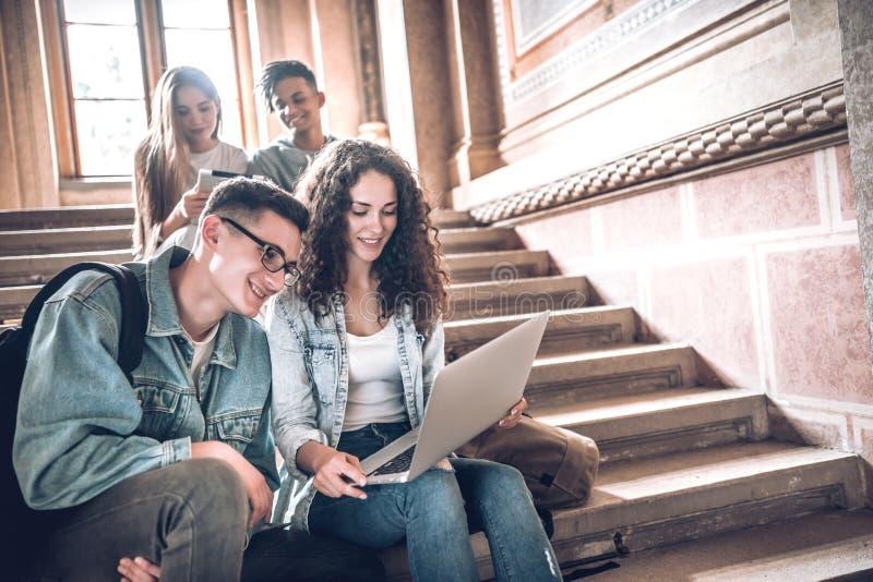Vida da faculdade Grupo de estudantes que usam um portátil ao sentar-se em escadas na universidade foto de stock
