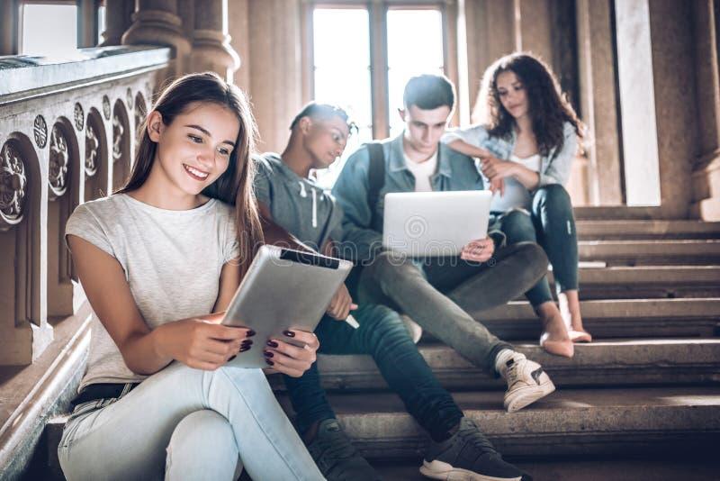 Vida da faculdade Um estudante novo bonito que senta-se em escadas no terreno usando a tabuleta quando seus amigos trabalharem co foto de stock royalty free