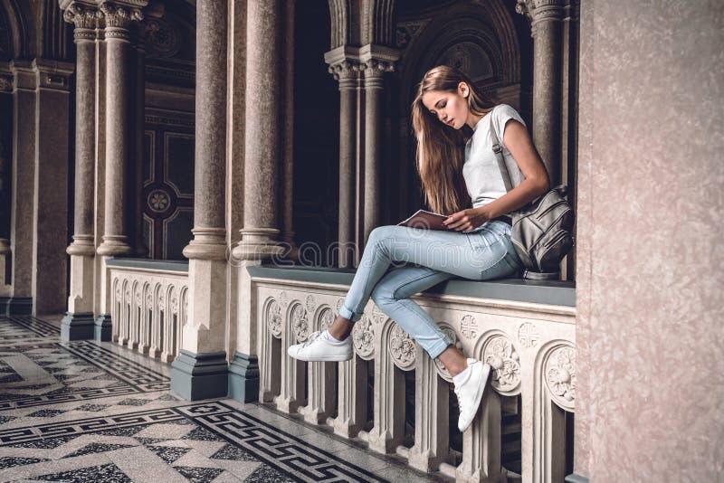Vida da universidade Estudante fêmea novo que senta-se nos trilhos no livro do salão e de leitura da universidade imagem de stock royalty free