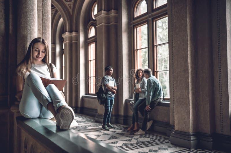 Vida da universidade Mulher bonita que senta-se nos trilhos que preparam-se para exames fotos de stock