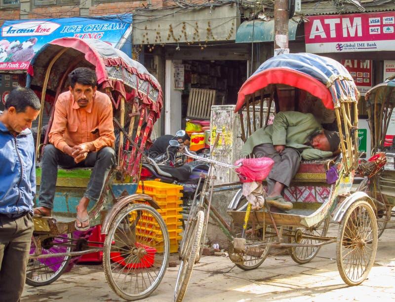 Vida de cada día del rikshaw capital de la gente de Katmandu Nepal foto de archivo