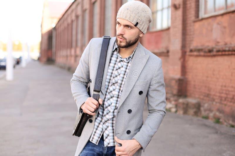 Vida de ciudad Hombre joven elegante en capa y sombrero grises que camina en la calle en la ciudad imagen de archivo