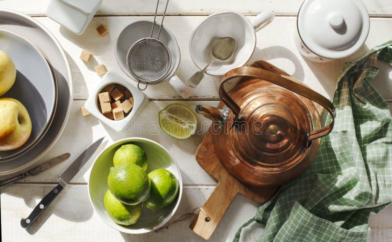 Vida de la calma de la cocina con la caldera de cobre, los utensilios de cerámica y las frutas en día soleado imagen de archivo