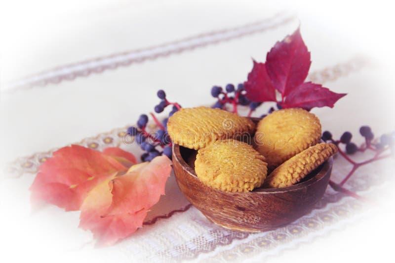 Vida de la calma del otoño con las galletas en una placa de madera y hojas azules del baya y anaranjadas imagen de archivo libre de regalías