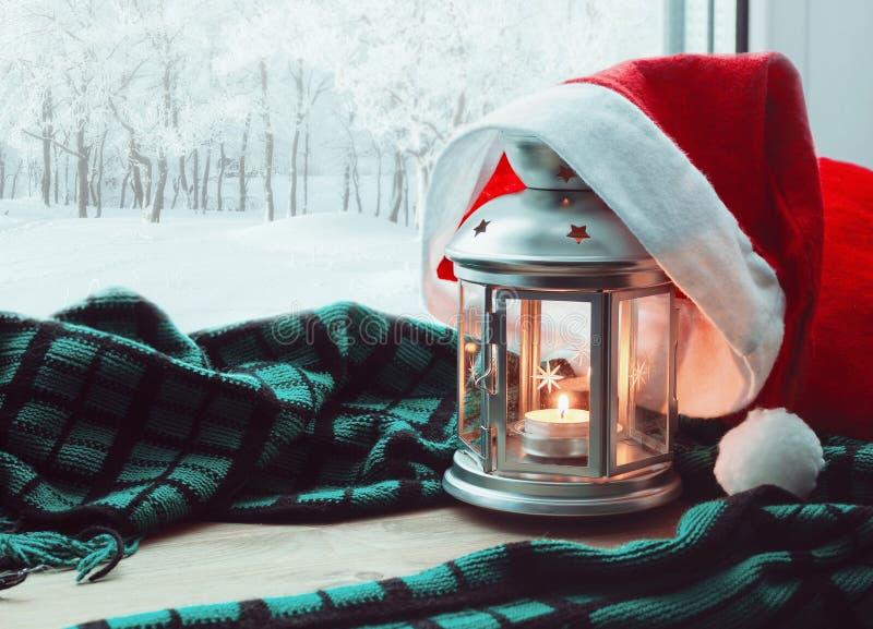 Vida de la Navidad tranquila festiva y todavía del Año Nuevo - linterna con la vela y el sombrero de Papá Noel y el parque del in fotografía de archivo