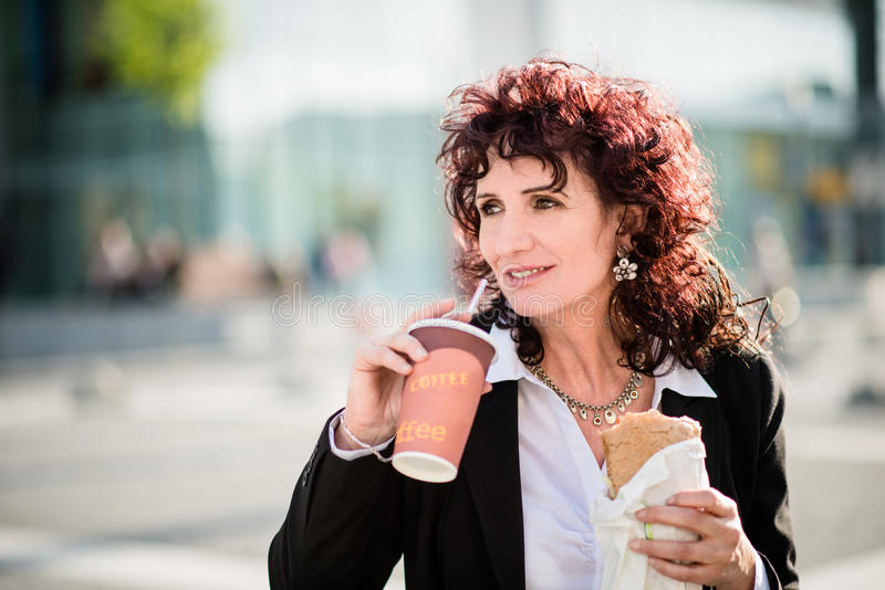 Vida de la prisa - mujer de negocios que come en calle imagen de archivo