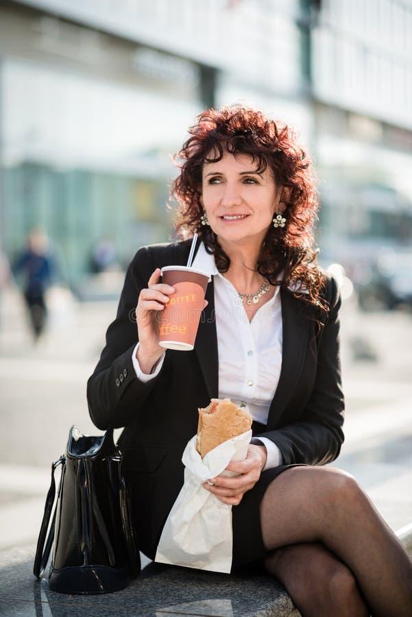 Vida de la prisa - mujer de negocios que come en calle imagenes de archivo