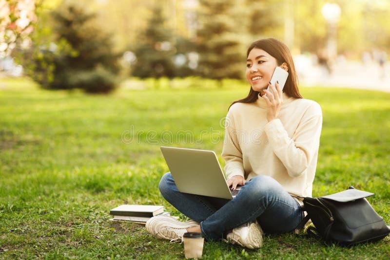 Vida de la universidad Muchacha del estudiante que habla en el teléfono y que usa el ordenador portátil imagenes de archivo