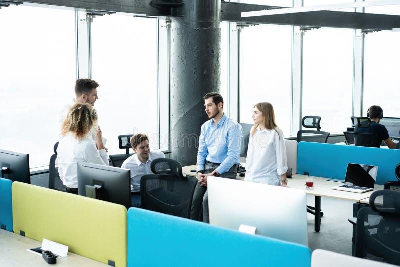 Vida do escrit?rio Grupo de executivos novos que trabalham e que comunicam-se junto no escrit?rio criativo fotografia de stock royalty free