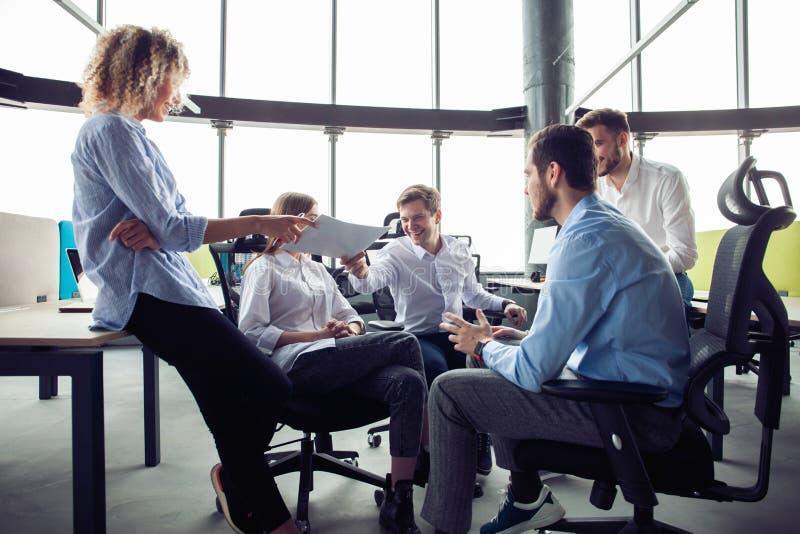 Vida do escrit?rio Grupo de executivos novos que trabalham e que comunicam-se junto no escrit?rio criativo foto de stock royalty free