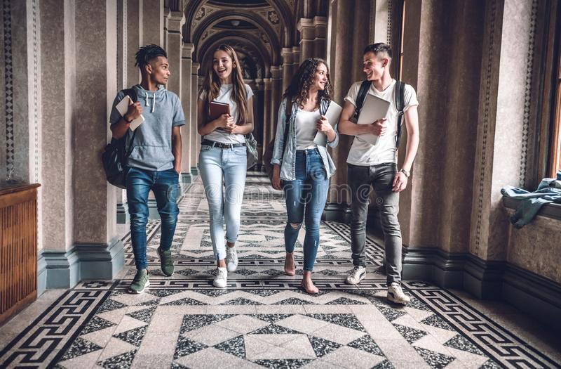 A vida do terreno é impressionante! O grupo de estudantes está andando no salão e na conversa da universidade imagens de stock royalty free