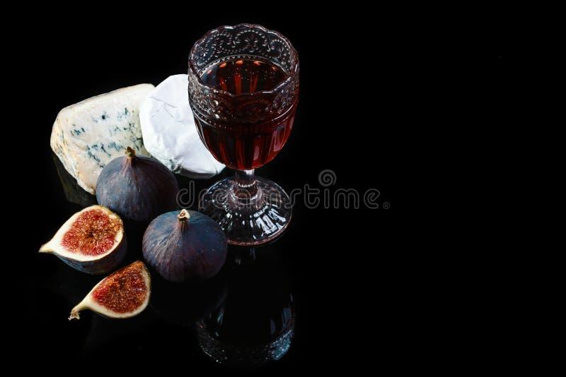 Vida do vinho, do queijo e dos figos ainda em um fundo preto do xisto da reflexão, espaço da cópia imagem de stock