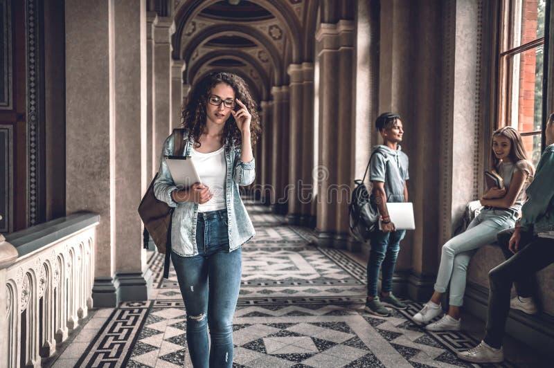Vida dos estudantes Estudante fêmea novo que vai na universidade e que ajusta vidros imagens de stock royalty free