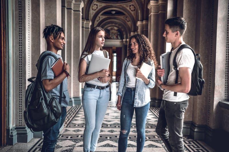 Vida dos estudantes Quatro estudantes bonitos que conversam-se na universidade fotos de stock royalty free
