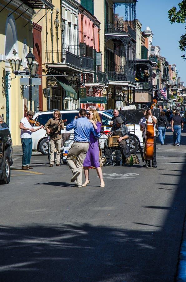 Vida en las calles en New Orleans con jugar de la banda de jazz y el baile de los pares imágenes de archivo libres de regalías