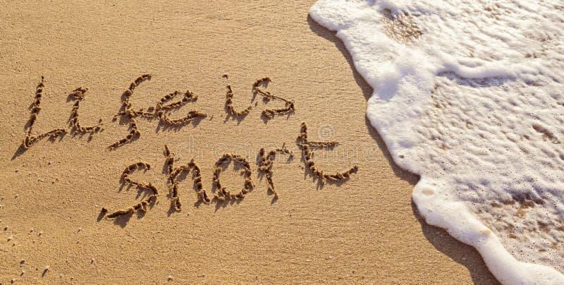 A vida escrita à mão da inscrição é curto na areia com nivelamento da onda espumosa fotografia de stock royalty free