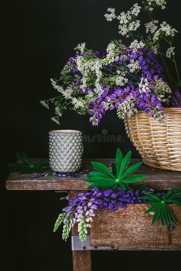 Vida escura do destilador do humor com flores selvagens e um copo em uma tabela do vintage fotos de stock