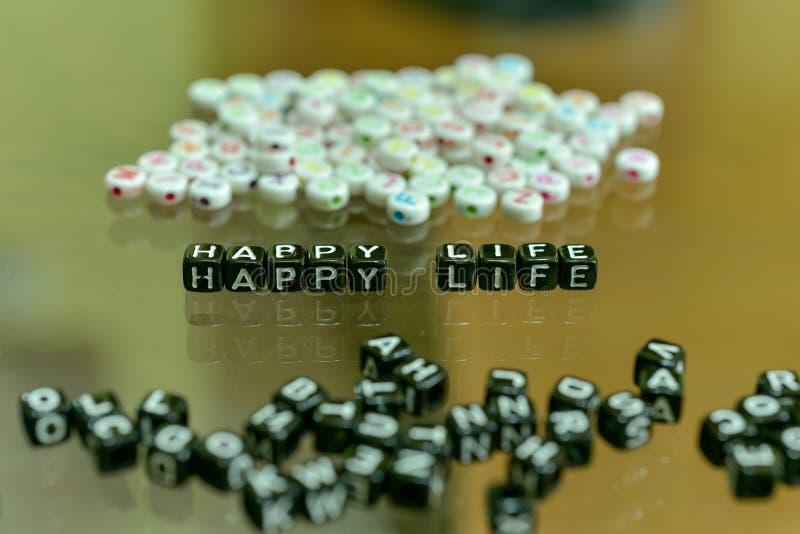 VIDA FELIZ escrita con el cubo negro de acrílico con las gotas blancas del alfabeto en el fondo de cristal fotos de archivo libres de regalías