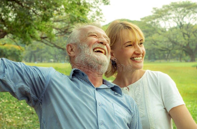 Vida feliz, par mayor que goza pasando el tiempo junto, hablando con la cara sonriente y riendo con lleno de amor fotografía de archivo
