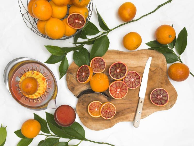 Vida imóvel bonita com as laranjas pigmentadas no fundo do Livro Branco e placa de madeira e faca imagem de stock