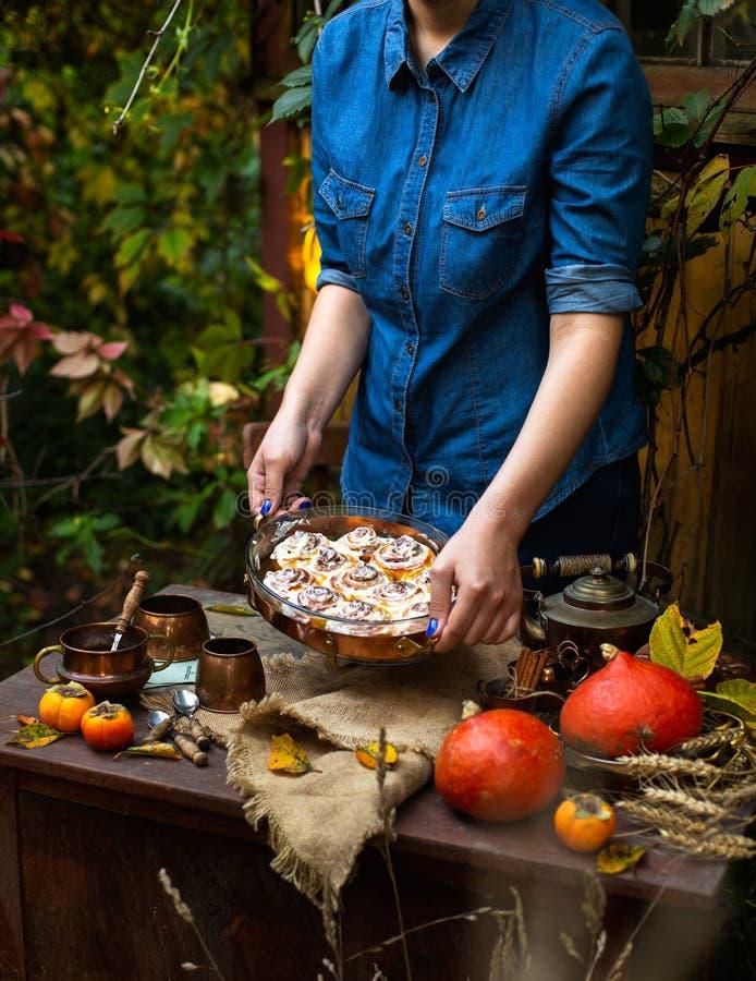 Vida imóvel bonita com os bolos de canela caseiros da abóbora no prato de vidro oval nas mãos da mulher fotos de stock royalty free