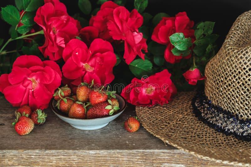Vida imóvel do verão com rosas vermelhas, morangos e um chapéu imagem de stock
