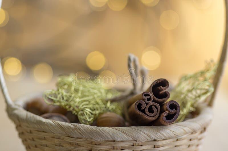 Vida imóvel do Xmas em claro - cesto marrom, varas de canela cruas, estrelas metálicas amarelas, reflexões das luzes de Natal imagens de stock